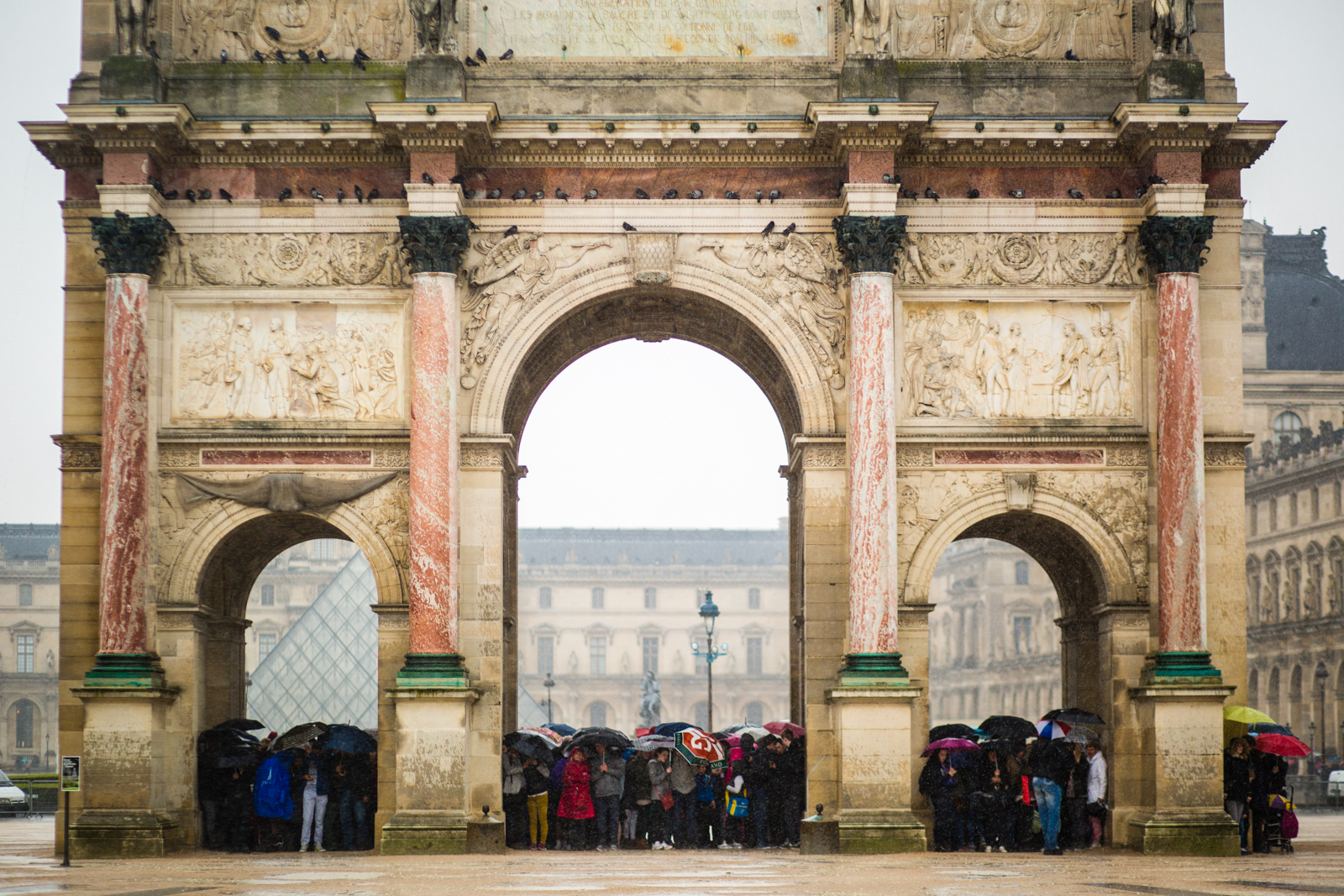 Tourists seeking shelter during a downpour, Arc de Triomphe du Carrousel, Paris
