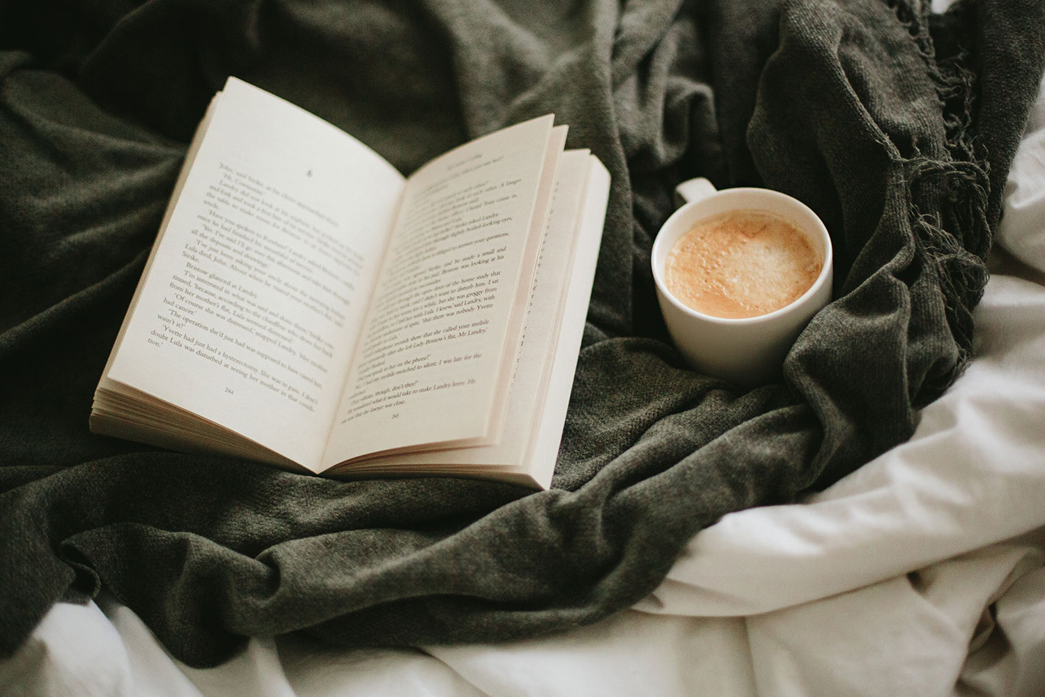 book and coffee mug on top of a bed